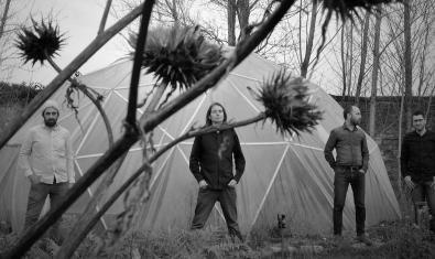 Los miembros de la banda retratados en blanco y negro en un bosque alrededor de una estructura geodésica