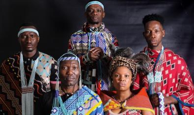 Retrato del bailarín y coreógrafo Gregory Maqoma y de los cantantes que lo acompañan vestidos con ropa de estilo africano