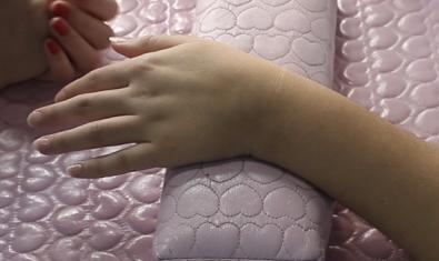 Imatge d'una mà mentre està sent sotmesa a un tractament de manicura