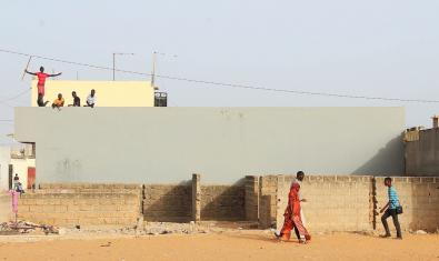 Imagen de un pueblo senegalés, con gente que anda por la calle y unos jóvenes que les miran desde una azotea