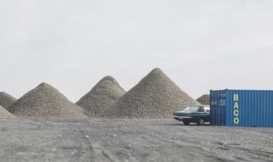 Uno de los paisajes a escala de Iván Franco que muestra un vehículo medio oculto tras un contenedor junto a unas montañas de arena