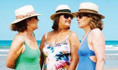 Tres dones amb vestit de bany, barret i ulleres de sol retratades a la platja