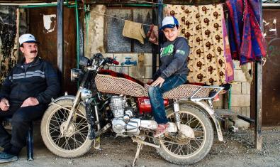 Una de les imatges de la fotògrafa mostra un nen refugiat pujat en una motocicleta