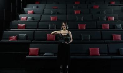 Una chica sostiene un aparato de música en las manos ante el patio de butacas vacío de la sala
