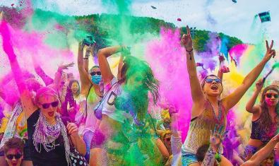 Un grupo de personas lanza al aire polvos de colores
