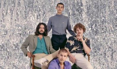 Retrato de grupo de los componentes de la banda contra un fondo psicodélico