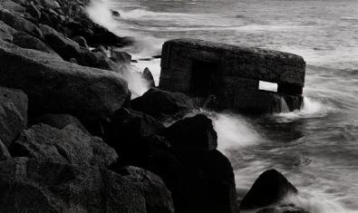 Una de les imatges de l'exposició mostra un antic búnquer de la guerra civil entre les roques de la costa