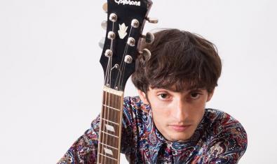 El músic mirant a càmera retratat amb la seva guitarra