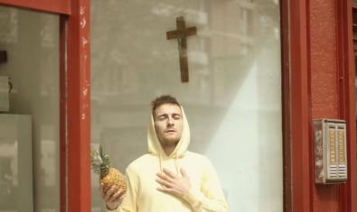 El actor protagonista con una piña en la mano y con cara de éxtasis ante un crucifijo