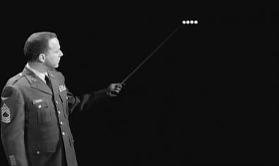 Un hombre con uniforme militar señala una transcripción Morse en una pizarra