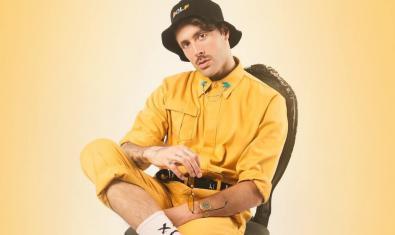 L'artista retratat assegut en una cadira vestit de color groc i amb una gorra
