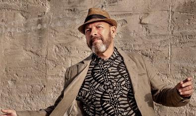 Retrato del artista con barba con un sombrero puesto y con la americana abierta