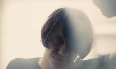 Retrat de l'artista a contrallum amb els cabells llargs i mirant directament a la càmera