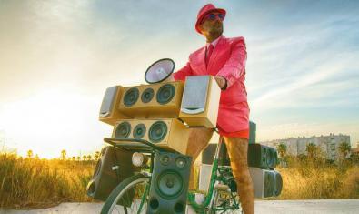 L'artista conduint una mena de bicicleta carregada de tota mena d'altaveus