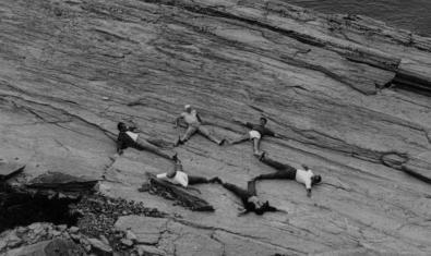 Una imatge de l'artista Jordi Mitjà que mostra un grup de gent formant una estrella sobre les roques a tocar del mar