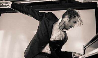 El músico retratado con el cabello recogido en plena actuación