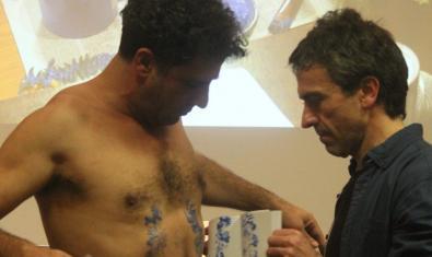 Uno de los intérpretes estampa un dibujo sobre la piel desnuda de su compañero en un momento de esta conferencia performativa