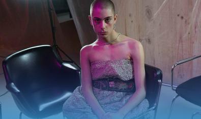 L'artista amb una arracada el cabell rapat i un vestit assegut en una cadira