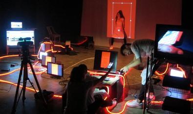 Una noia enfocada per tot de càmeres digitals i envoltada de dispositius electrònics en un moment de la representació