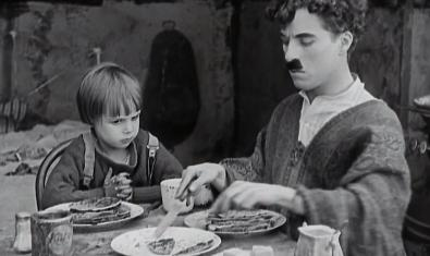 Fotograma de la película, Chaplin y el niño comiendo