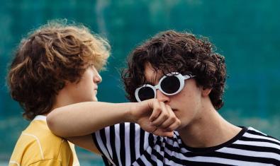 Els dos integrants de la formació recolzats l'un en l'altre i amb unes grans ulleres de sol posades