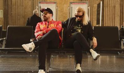 Los dos DJs retratados con gafas de sol y sentados en el vestíbulo de una estación