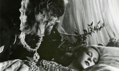 The half-man half-beast watching the beautiful woman asleep on the bed.
