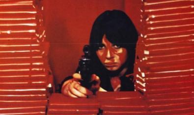 Una mujer escondida entre papeles apuntando con una pistola.