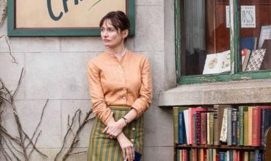 Una dona a la vorera del carrer recolzada a la paret, al seu costat hi ha un estant ple de llibres.