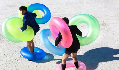 Els dos membres de la companyia retratats mentre caminen per la sorra d'una platja carregats de flotadors de colors diversos