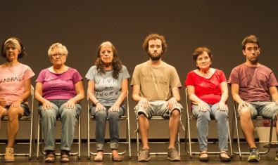 Sis dels artistes que protagonitzen el muntatge asseguts en unes cadires a l'escenari de cara als espectadors