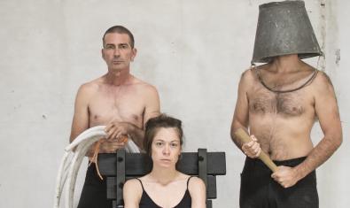 Retrat dels protagonistes de l'espectacle amb una noia asseguda en una cadira i envoltada de dos homes sense camisa un dels quals porta una galleda al cap que li cobreix la cara