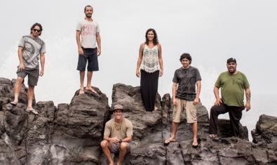 Los seis integrantes de la banda retratados en unas rocas junto al mar