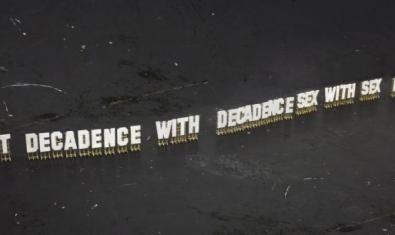 Una llarga frase escrita en grans lletres col·locades en cadires i fotografiada des de l'aire en una de les peces de l'exposició