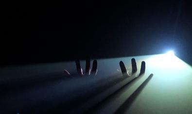 Dos manos emergiendo de la oscuridad en un momento de la representación