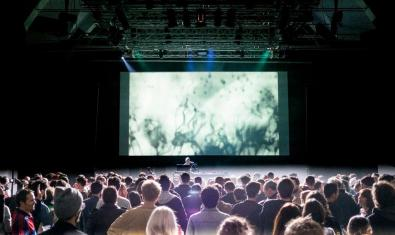 Un DJ sobre un escenari amb una gran pantalla amb projeccions al darrere i amb un públic nombrós al davant