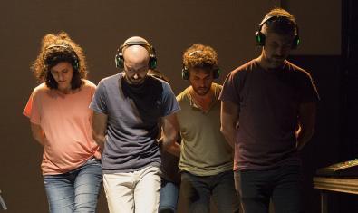 Cuatro actores y actrices de la compañía con unos cascos puestos en los oídos y la cabeza gacha en un momento del ensayo