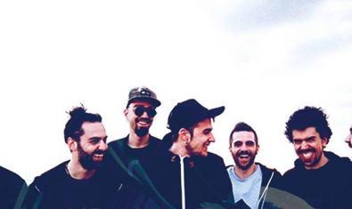 Retrato de grupo en exteriores de los siete miembros de la formación riendo y conversando entre ellos