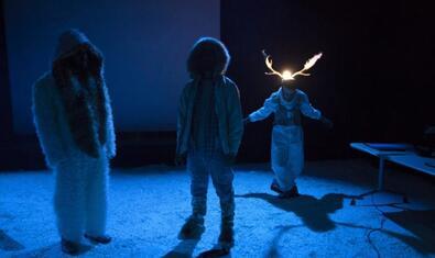Tres personatges un dels quals amb unes banyes de ren en un escenari blanc que simula ser un paisatge de l'Àrtic