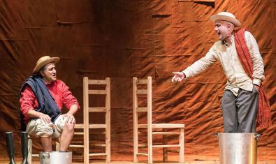 Els dos protagonistes de la funció en l'escenari portant barrets de palla i amb els peus en una galleda