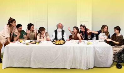 Els actors i actrius del muntatge asseguts al voltant d'una taula amb una paella al centre