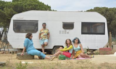 Los cuatro integrantes de la banda, retrados ante una caravana