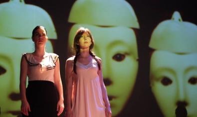 Les dues actrius protagonistes dempeus sobre l'escenari davant d'un fons que mostra unes grans màscares