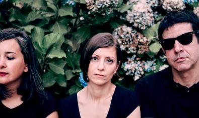 Els tres integrants de la formació retratats contra un fons de flors naturals
