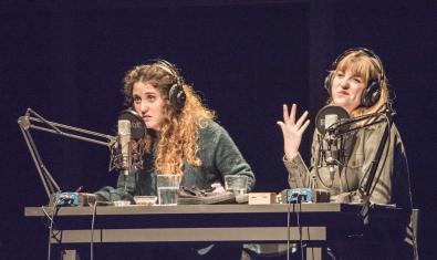 Les dues actrius protagonistes interpretant el muntatge assegudes en una taula i davant de dos micròfons de ràdio