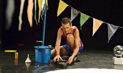 El coreógrafo agachado y manipulando un objeto en un momento de la representación
