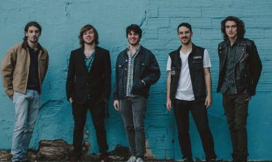 Retrato de los cinco miembros de la banda contra un muro de la calle