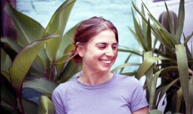 L'artista retratada somrient i envoltada de plantes