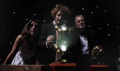 Tres personajes contemplan las proyecciones de una linterna mágica
