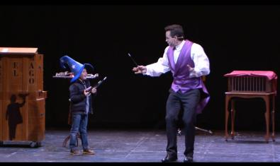 Uno de los magos con un niño en el escenario